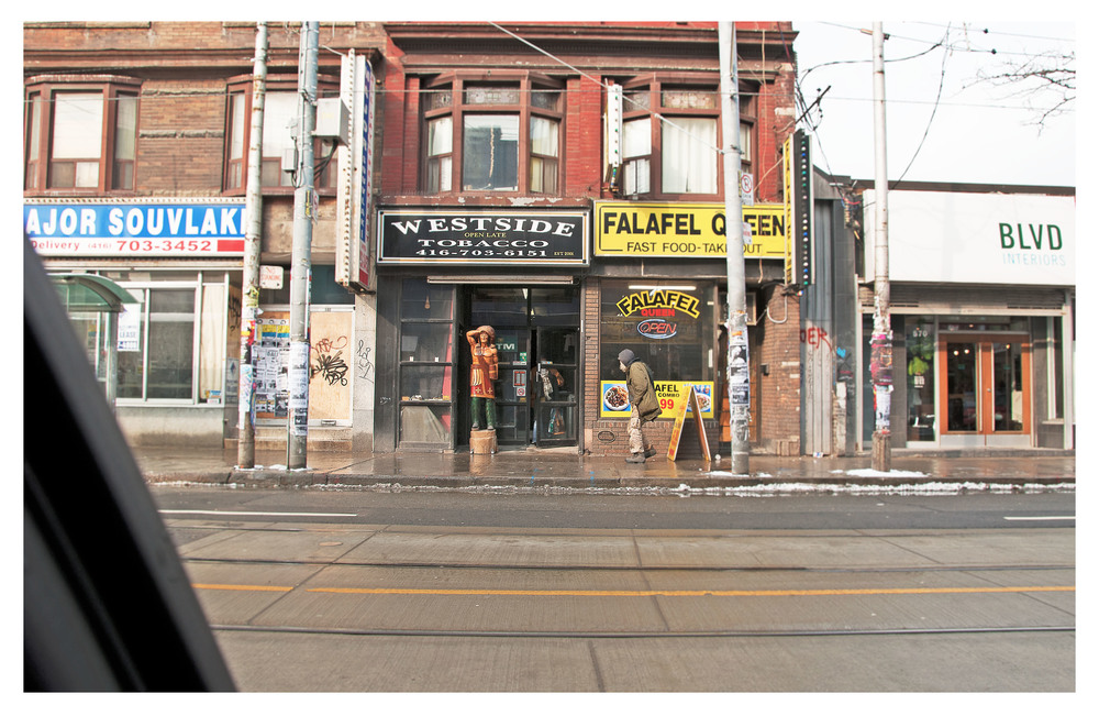 30. Toronto, Ontario,  drive-by view of Cigar store Indian and street person, Queen St and Bathurst .jpg