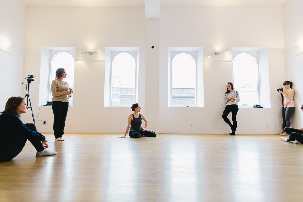 Image of 6 people in a bright studio. Some sit on the floor and others stand or lean against the 4 windows. Photo credit: Michelle Peek.