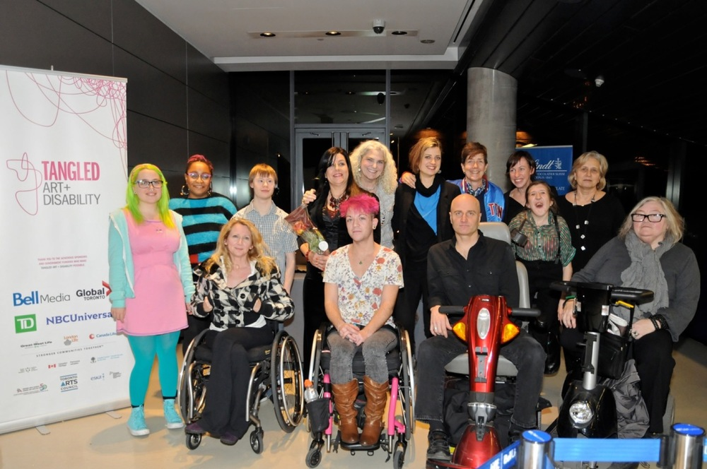 A group of people, some standing and others in wheelchairs, pose and smile for the camera next to a retractable banner for Tangled Art + Disability.
