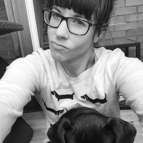 Black and white image of Kimber Side. She is wearing rounded square glasses and has dark hair with bangs. She is making a sassy expression at the camera. She is wearing a white long sleeved shirt with dachshunds on it. There is a dachshund in the foreground.