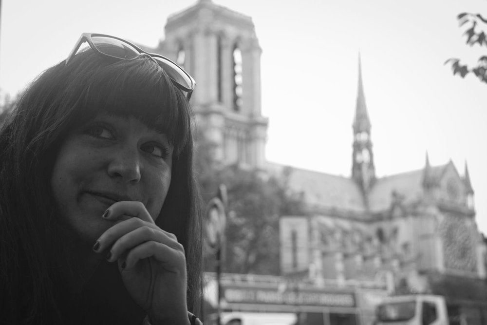 Black and white image of Andrea LaMarre. She is sitting outside of Notre Dame cathedral. She is looking up to the right and her left hand is by her mouth. She has dark hair and bangs and sunglasses on her head.