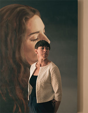 Photo of Eliza Chandler standing in front of a paining of a person with long hair in profile. Eliza is wearing a white jacket and a black shirt and has short, dark hair.