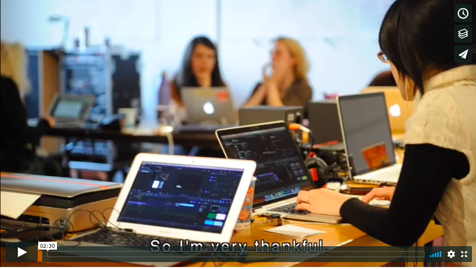 Screenshot from the REDLAB promotional video, with several people sitting at tables working on laptops.