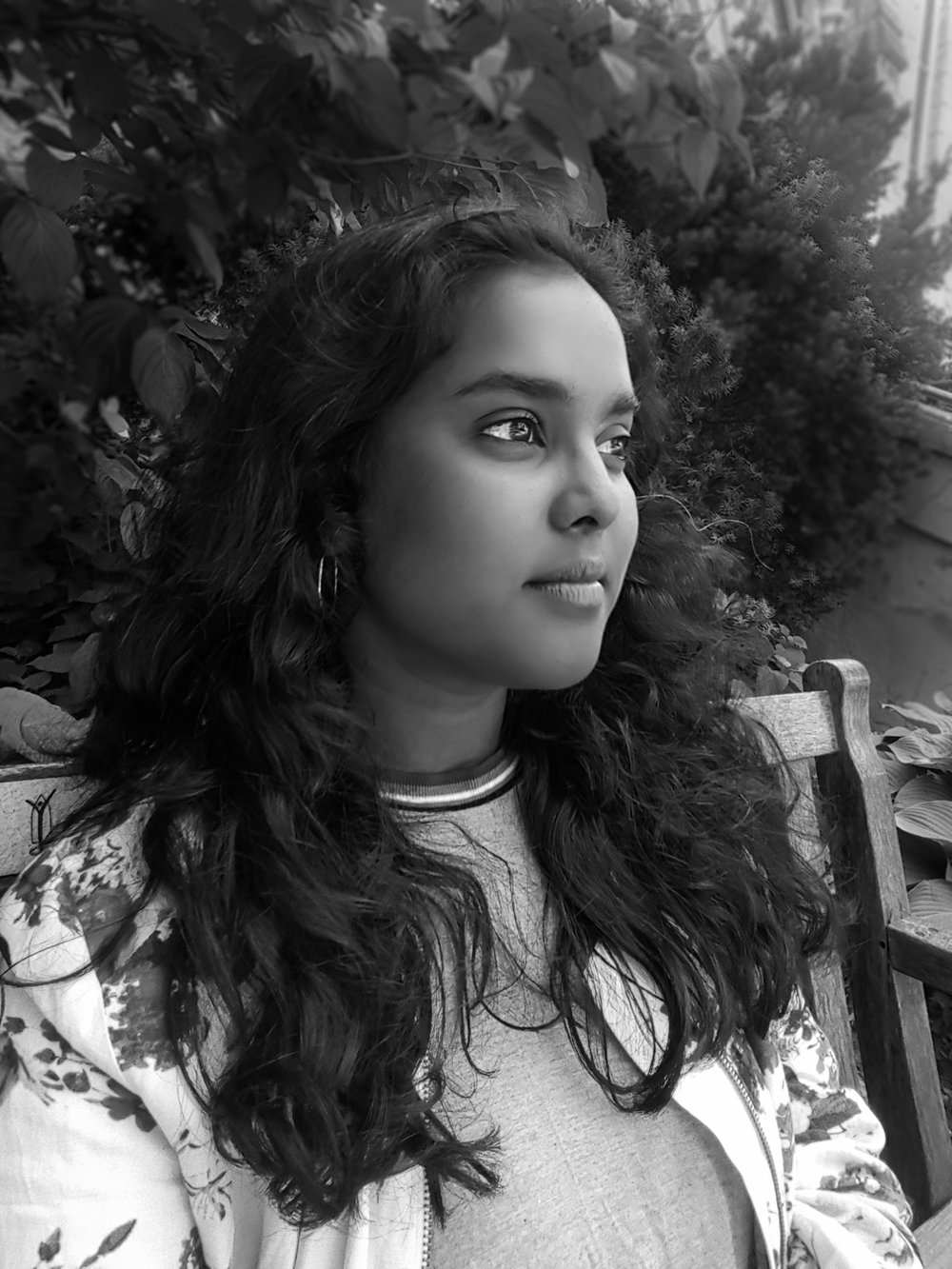 Black and white photograph of Kavya Yoganathan. She is in 3/4 profile, and has dark wavy hair.