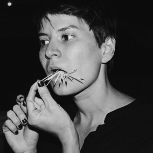 A black and white photo of Vanessa. She has short dark hair and painted fingernails. Vanessa's eyes are fixed on something in the distance, while porcupine quills jet out of her mouth and her fingers delicately pick one to remove.