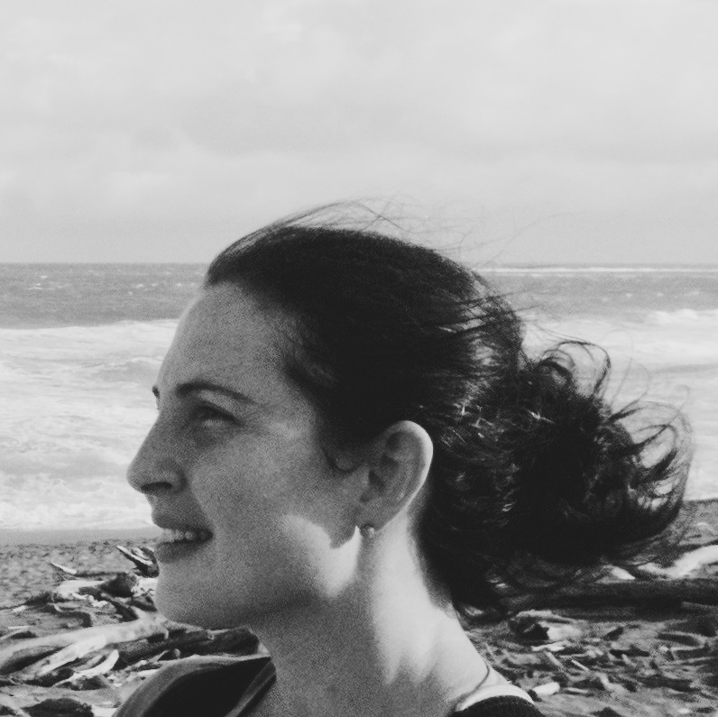 A black and white side-profile portrait of Evadne Kelly. She is on a beach, with her dark hair tied back from her face, blowing in the wind. She faces to the left, smiling and looking into the distance.