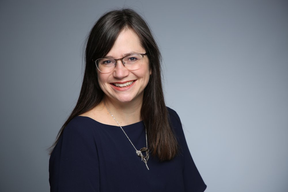 Photo of Sally Chivers, professional headshot-style featuring a middle-aged, brunette, long-haired, smiling woman with glasses, head and shoulders tilted slightly toward the camera. She's wearing a navy top with a silver necklace.