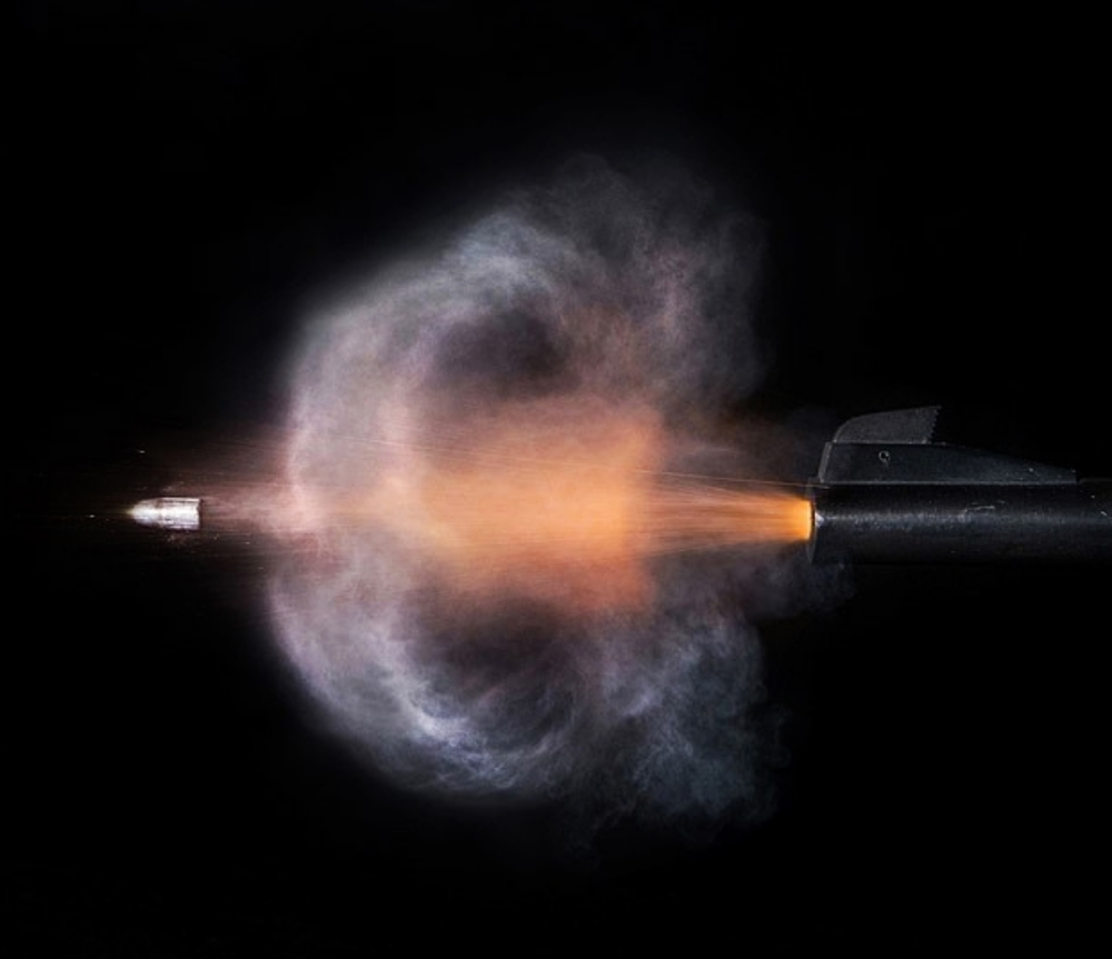 Microsecond photo of a bullet leaving the muzzle