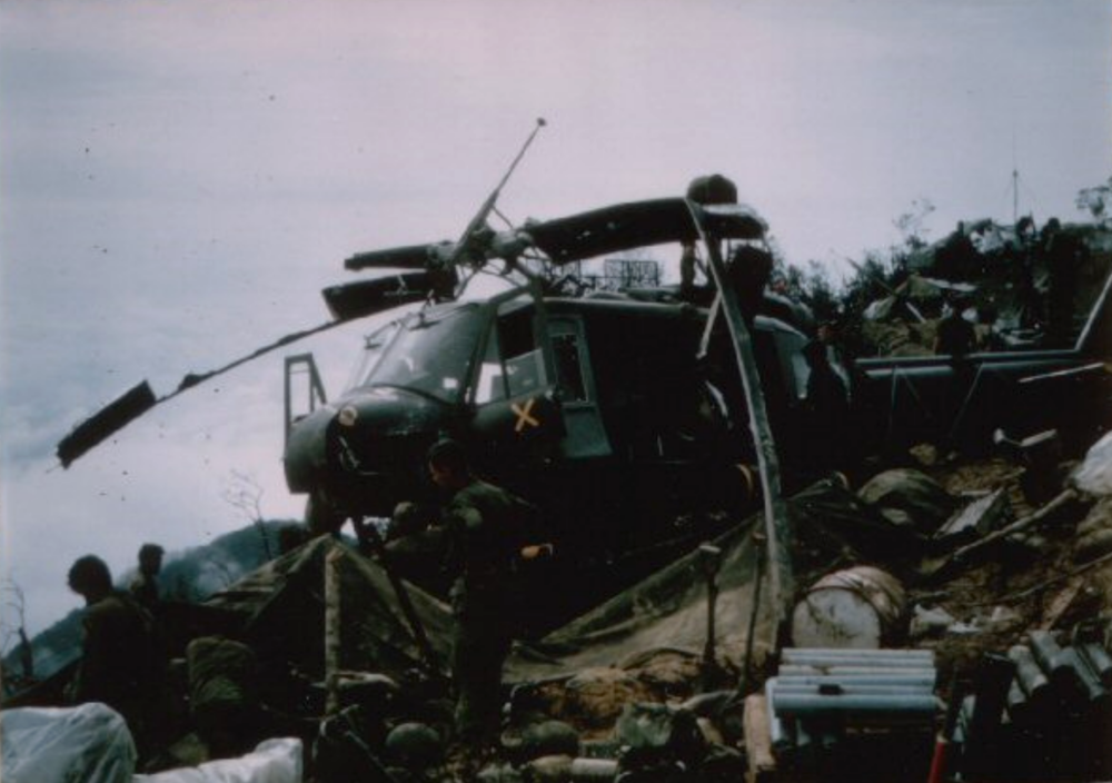 """Signal Hill, second crashed Huey. The two crossed sabers painted in gold across the nose, and a large """"X"""" on the doors, indicated it was a command ship from the 1st Squadron, 9th Cavalry, our division's most elite aviation force"""