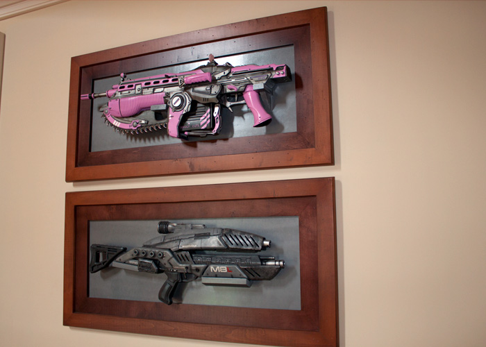 TOP: Lauren's 1 of a kind pink lancer made by  Triforce  and given to her by Clifford for her birthday at Comic Con.  BOTTOM: Lauren's M-8 avenger assault rifle from Mass Effect Series!   (These are right outside the game room, in the hallway.)