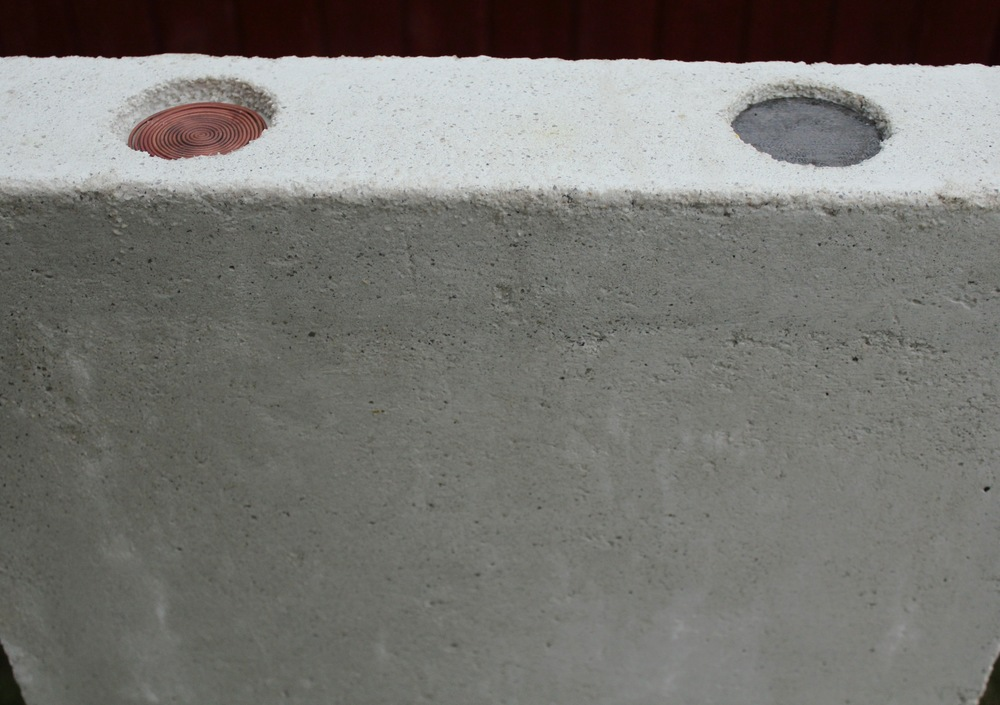 """Universe Painting"" is a monothithic block of white concrete, formed into two cups on the top edge. These voids, inconspicuous at eye level, contain steel and   copper, that are intended to stain the concrete as the cups collect rain and the metal   corrodes over time."