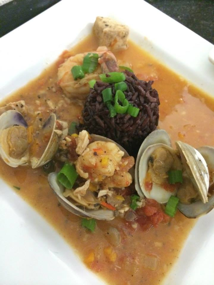 First Entree: Holiday Boullibase - Halibut, Clams and U-ro Shrimp in a broth of pressed tomato and chardonnay cream; volcanic purple rice filled with vinaloo carrots