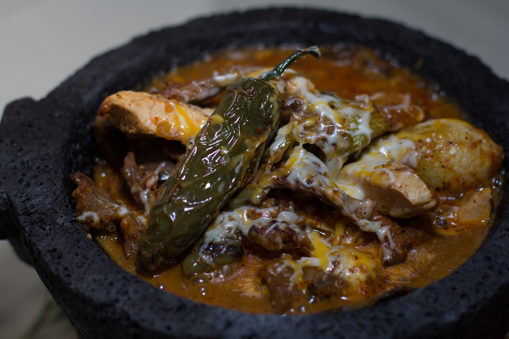 "Our signature dish, The Molcajete. Grilled chicken, steak & chorizo; grilled cactus, onions & peppers; with Oaxaca cheese, all served in a sizzling hot molcajete, and with handmade corn tortillas, rice & beans.  Like Charlie at U.S. Kustoms says, ""It'll Save Your Life!"""