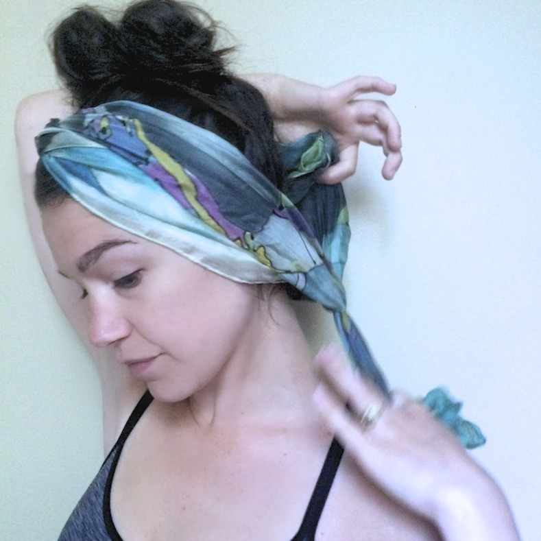 Pull the twist tight and wrap end behind head, double knotting at the nape of your neck. Tail ends may be kept loose or tucked into the sides of the wrapped scarf.