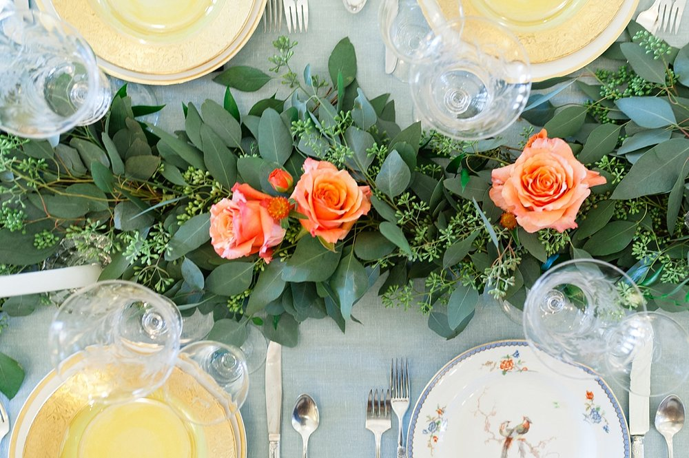 A lush runner of seeded eucalyptus with minimal accents of orange roses decorating the head table (photo by  Roots of Life ).