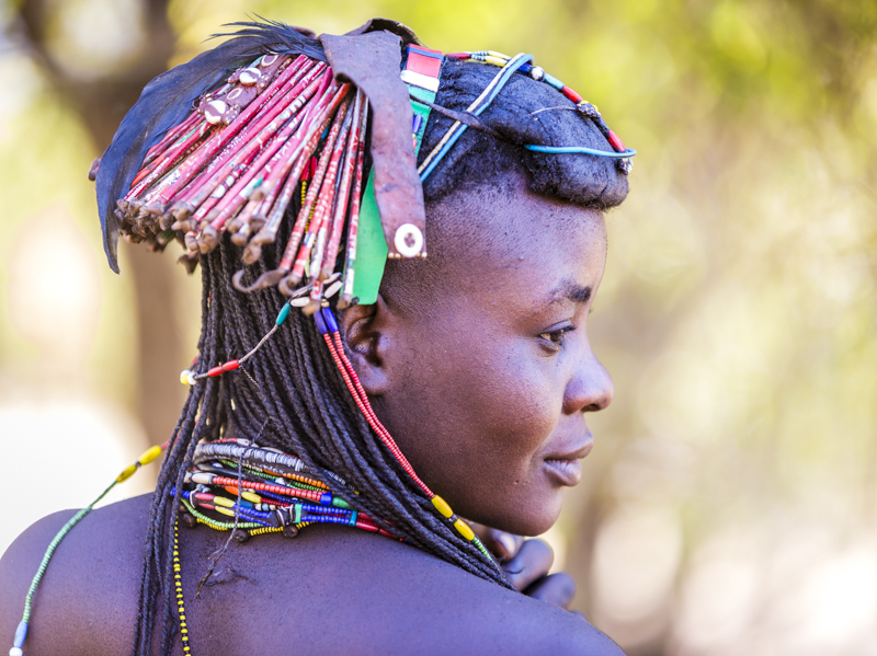 "In a world where there are no facilities, everything gets used.  Here the Mucawana decorate their hair with ""ringlets"" made from Coca-Cola tins.  Soba, Cunene Province   ©24Atlantic"
