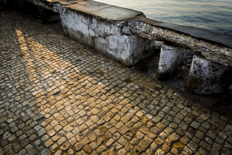 Cobblestone sidewalks, crumbling walls... remnants of Portugese Colonialism.  Lobito, Benguela Provence   ©24Atlantic