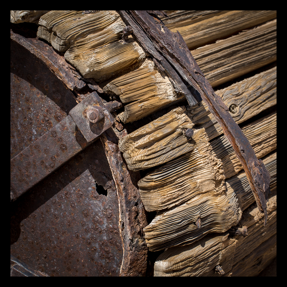 Sand eroded wood and rusted strapping around water drums