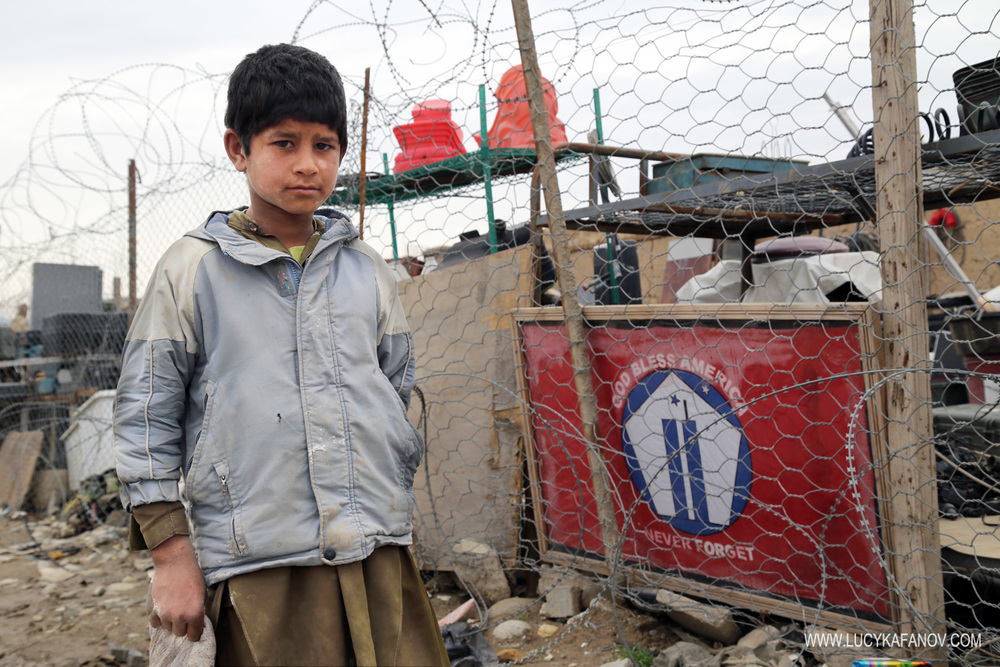 A boy stands outside one of the Bagram scrapyards.