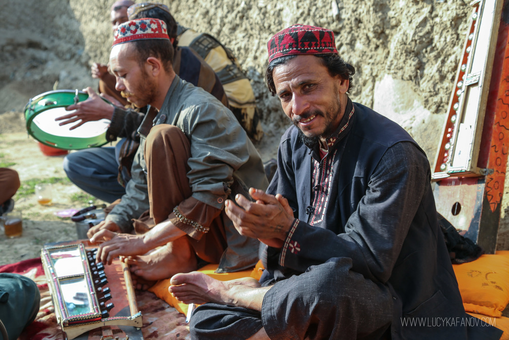 A group of men play traditional music from Afghanistan's southern Helmand Province. The instrument you see here is called a japoni. The man playing it arrived to this IDP camp in Kabul only three days ago. The Taliban have taken over his village, he said, and it was too dangerous to remain.
