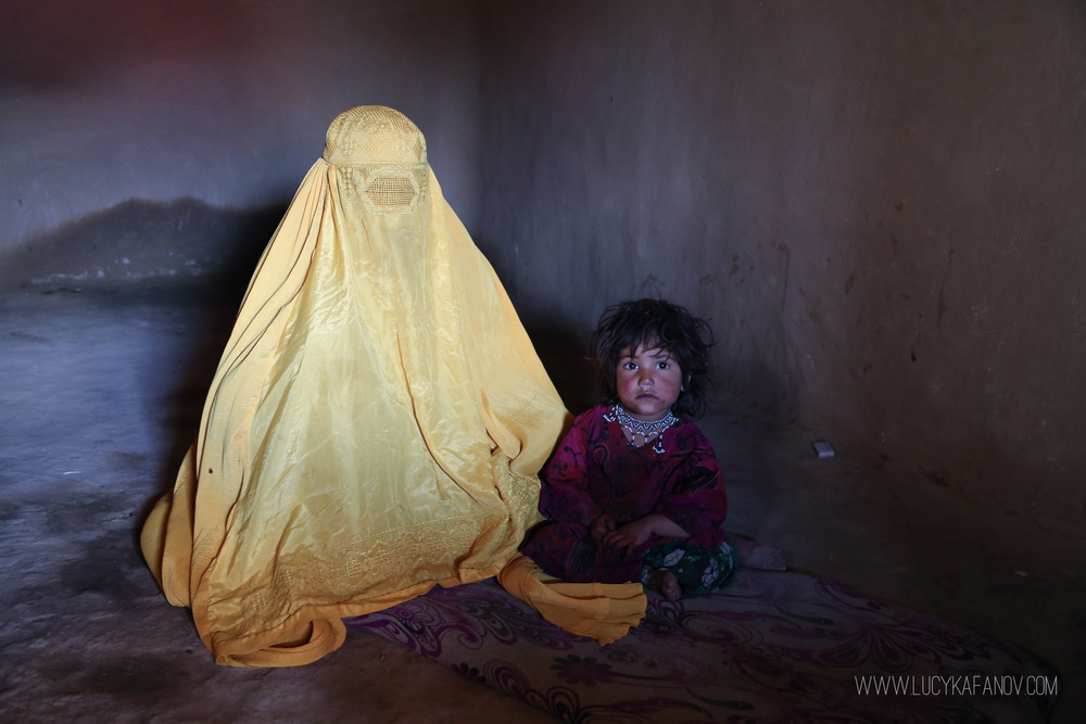 A mother and daughter sit inside their bare mud brick home. They were forced to leave all of their possessions behind when fighting erupted in the Sangin District of Helmand Province. With job opportunities scarce in Kabul, their economic situation remains dire.