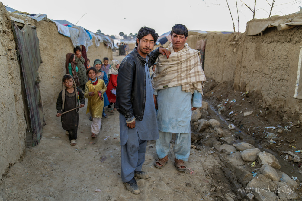 A group of Afghans stand on the street of this camp for internally displaced people.