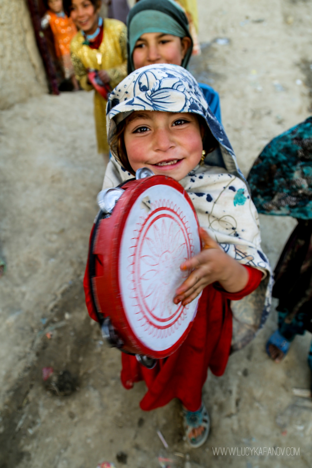 A young girl plays the tambourine on the narrow street of the IDP camp.