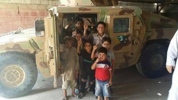 Children pose next to U.S. Humvee obtained by ISIS from Mosul. via@EjmAlrai