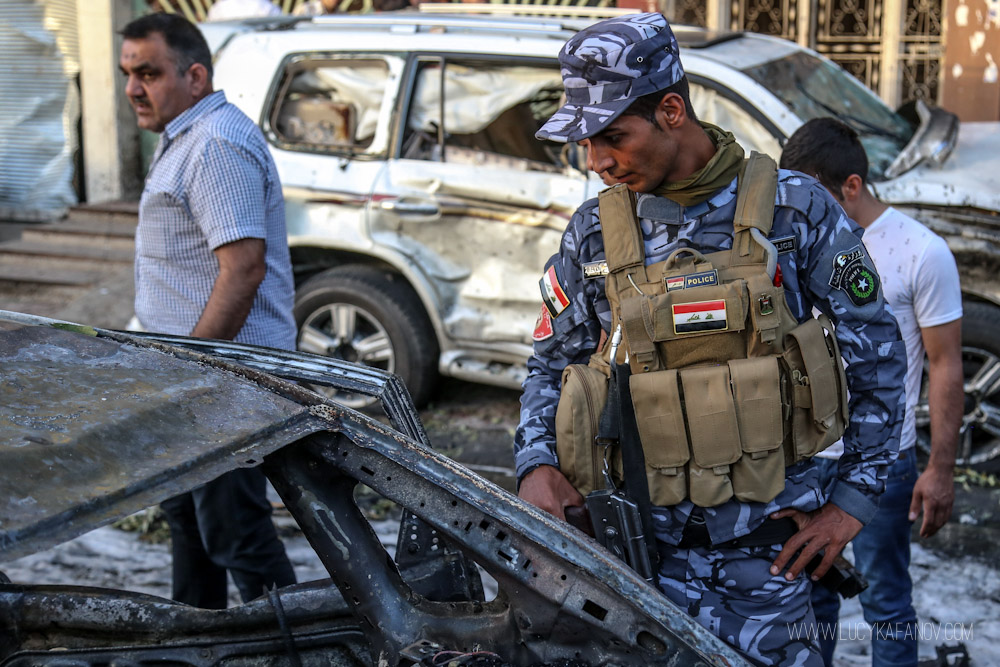 An Iraqi police officer surveys the remnants of a burned out car in Kirkuk. Photograph by Lucy Kafanov.