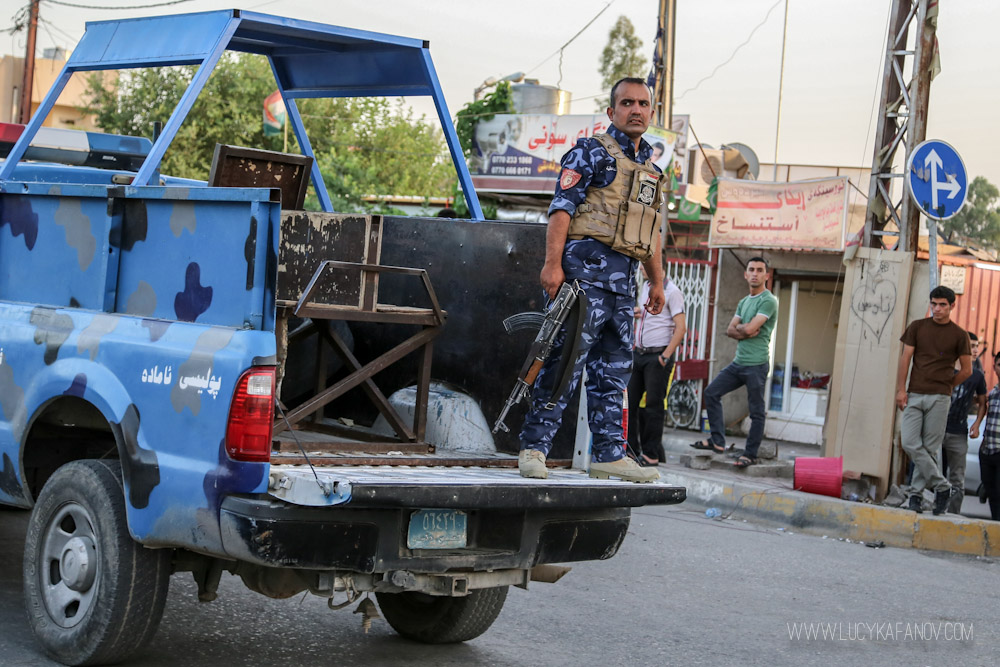 A Kirkuk police officer warily watches the scene. Tension is high and tempers have been flaring up. Moments earlier, Peshmerga soldiers fired their weapons into the air to scatter onlookers. Photograph by Lucy Kafanov.