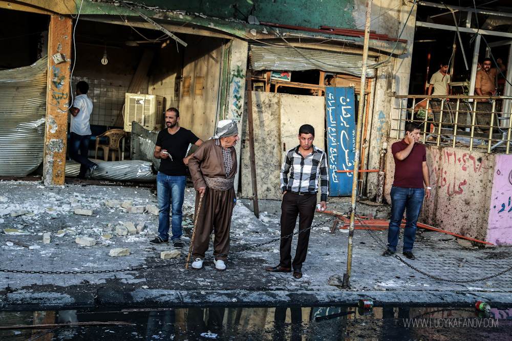 Stunned residents survey the damage. A suicide bomber detonated his vest on this busy market street in Kirkuk, Iraq. Photograph by Lucy Kafanov.