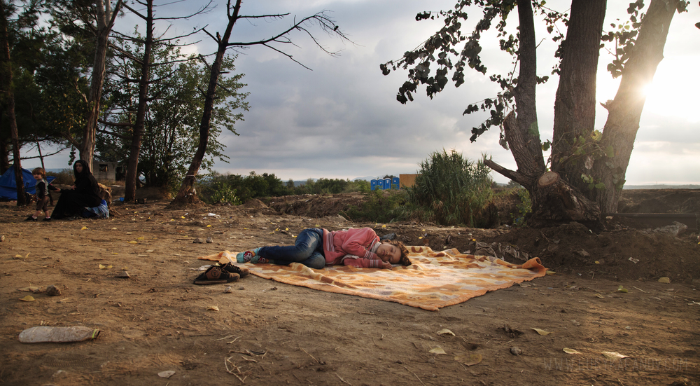 A young girl takes a nap as her family waits for the Macedonian-Greek border crossing to open.