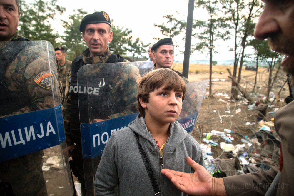 Surrounded by Macedonian riot police, a Syrian boy waits to cross into the country from Greece.