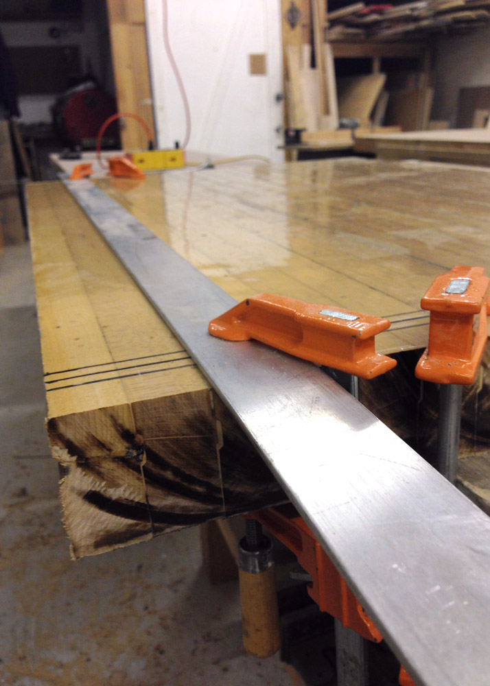 With the table saw was out of the question, I used a handheld circular saw to cut the piece down to size. To keep the cuts straight, I used a piece of scrap metal clamped to the wood. A nerve-wracking number of sparks flew all over the place every time I hit a nail.