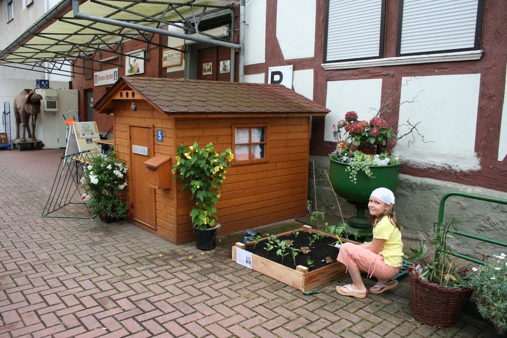 """Bäckerei Guido, Thiel, Selina(Pfleger),  Hersfelderstr 109,  Breitenbach         In Breitenbach vind ik een locale supermarkt met een stenen dorpsplein ervoor. Op dit plein staat een huisje van hout. Hier moet een tuin bij. Het huisje blijkt van Selina, een meisje met een roze hoofddoek van ongeveer 7 jaar oud te zijn. Ze laat me ook de binnenkant van het huisje zien; een kleine keuken met een echt fornuis. Werkelijk alles zit erin. Ze wil heel graag het tuintje. Haar vader blijkt ook enthousiast. Hij is de bakker van het dorp. Alleen zegt hij; """"gisteren was hier een Japanse kunstenaar met een project die nog zou terugkomen maar niet verschenen is"""". Hoe zit dit? Ik beloof het te checken .  Samen met Selina de volgende dag het tuintje gemaakt. Haar vader, de bakker, laat hun huis zien en vertelt over de geschiedenis van de vakwerkhuizen in dit dorp. Ook heeft hij net een oud en vervallen vakwerkhuis gekocht. Hij wil dit afbreken om er een park van te maken voor het dorp. Dat is wel heel bijzonder iemand die een huis koopt om er een park van te maken; een sociale groenfanaat; heel erg leuk. Ook krijg ik van hem als dank een tas met brood en koekjes!"""