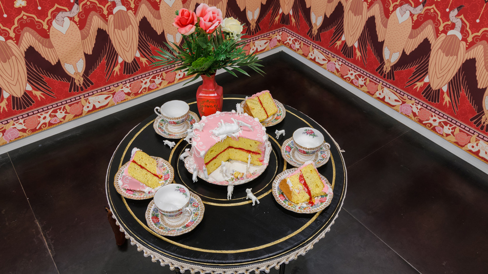"Eat,  2016 Bamboo Chinoiserie table, Victoria cake with icing, animal cake toppers, Royal Standard bone china tea cups and saucers in ""Indian Summer"" pattern, plastic flowers, vase, bamboo perches with gold rope and tassels, wallpaper dimensions variable"
