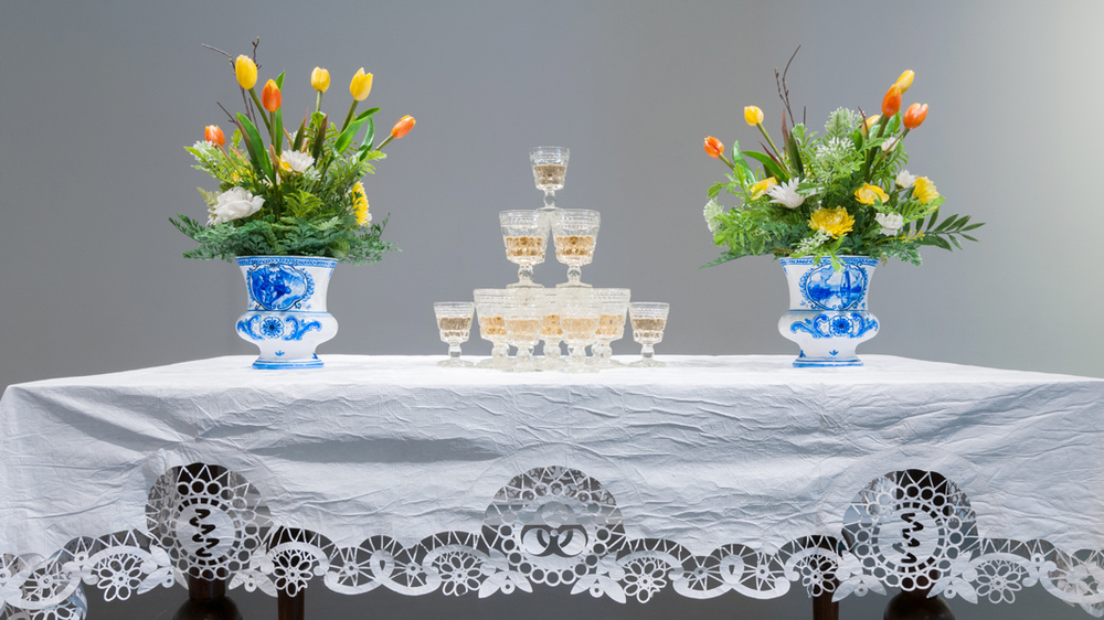 Drink  (detail), 2016 Brass chandelier with fruit-bat crystals, 17th century-Dutch-style table, Tyvek® table cloth, stemware with wine, hand-painted Delftware-style vases with plastic flowers imensions variable
