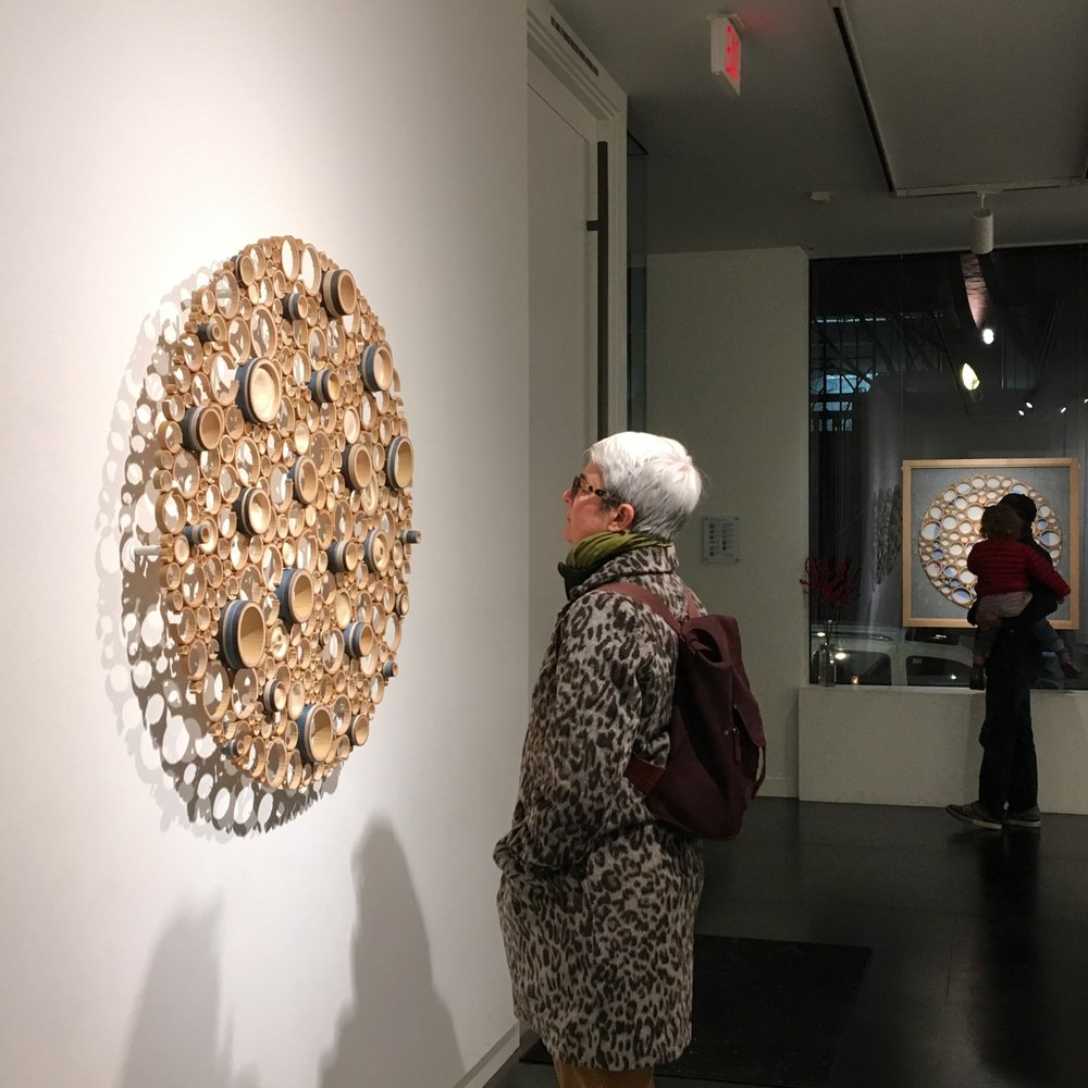 Gallery visitor contemplating a crosscut bamboo sculpture by Anne Crumpacker during the First Thursday art walk.