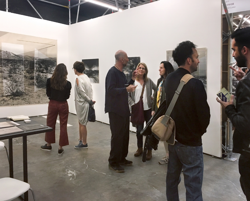 Fair-goers perusing Upfor's presentation of works by Rodrigo valenzuela.