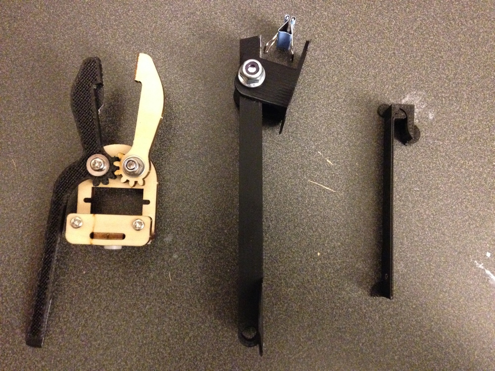 """The first attempts tried to grip the binder clips but this proved to be unstable and require too much force. Longer and stronger lever arms didn't change the instability of the binder clip. The far right design was an attempt to 3D print a """"clothespin"""" but it didn't offer enough force."""