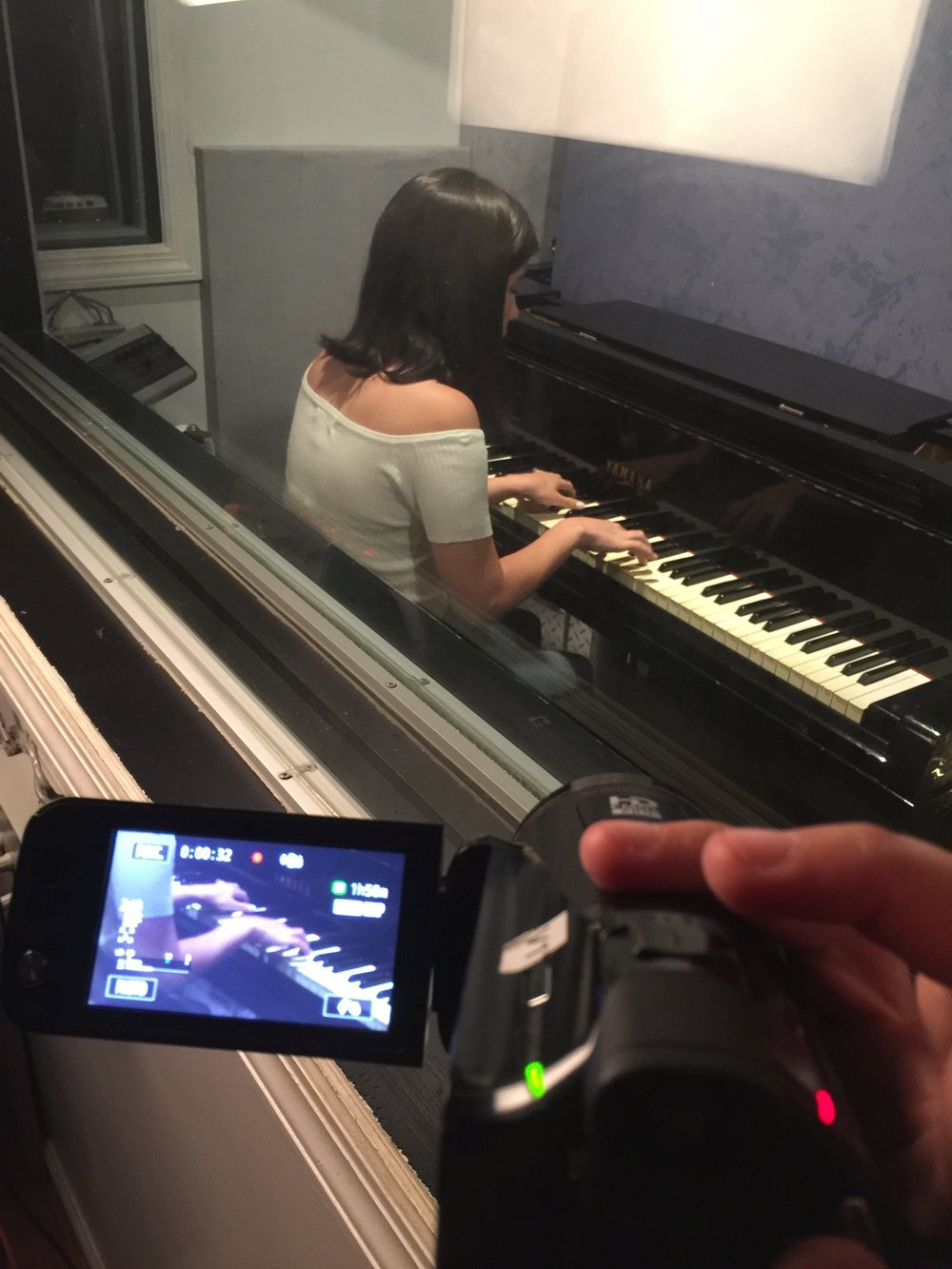 a handheld camera from the drum room to get close up on the pianist's hands.