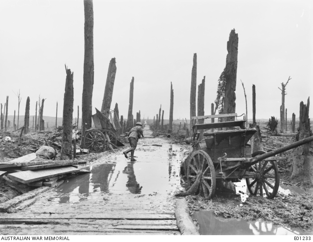 The debris lined road through Chateau Wood to Westhoek Ridge, in the Ypres sector. An unidentified soldier runs across the road between two abandoned limbers and piles of wood. The wood is comprised of denuded tree trunks, bare of branches. Belgium: Western Front (Belgium), Menin Road Area, Chateau Wood. 5 November 1917.