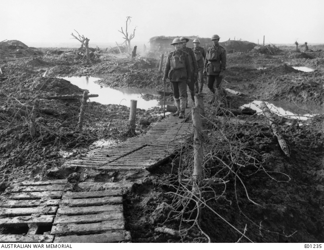 Four unidentified soldiers walking along a duckboard track across the otherwise impassable mud at Garter Point, near Zonnebeke, in the Ypres sector. The wire entanglements fronted the recent German line, prior to its capture by the Australian troops. Belgium: Western Front (Belgium), Menin Road Area, Garter Point. 22 October 1917.