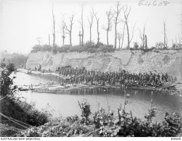 A large group of unidentified Australian troops resting along the town's moat and ramparts. The following day marked the entry of Australian troops into the Third Battle of Ypres, with the 1st and 2nd Australian Divisions taking part in operations. The entrances to the dugouts, built into the ramparts, can be seen behind the soldiers. Belgium: Western Front (Belgium), Ypres Area, Ypres. 19 September 1917.