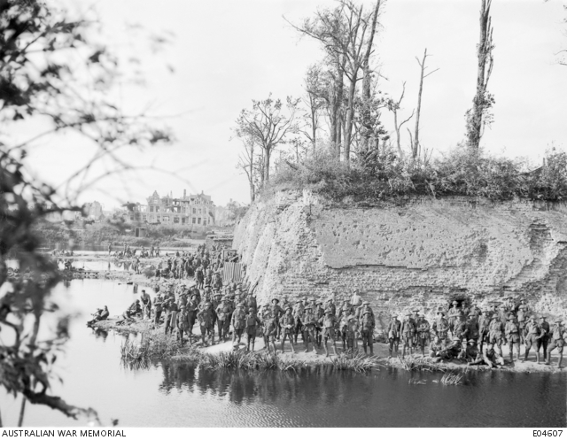 A large group of unidentified Australian troops resting near the famous moat and ramparts of the town. The following day marked the entry of Australian troops into the Third Battle of Ypres, with the 1st and 2nd Australian Divisions taking part in operations. Note in the background the dugouts built into the ramparts (centre) and several shell damaged buildings. Belgium: Western Front (Belgium), Ypres Area, Ypres. 19 September 1917.