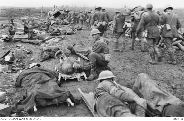 Men wounded in the Ypres Battle waiting along the Menin Road to be taken to the clearing station. German prisoners are assisting with stretcher bearing. Belgium: Western Front (Belgium), Ypres Area, Ypres. 20 September 1917.