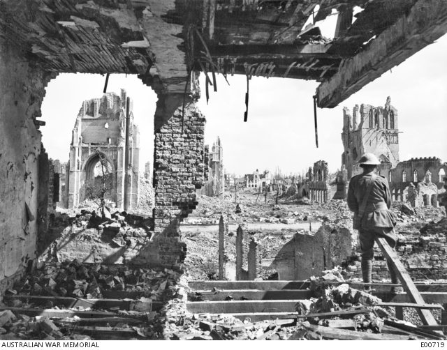 An unidentified Australian in the right foreground surveying the bombed building in the ruined city of Ypres. Belgium: Western Front (Belgium), Ypres Area, Ypres. 3 September 1917.