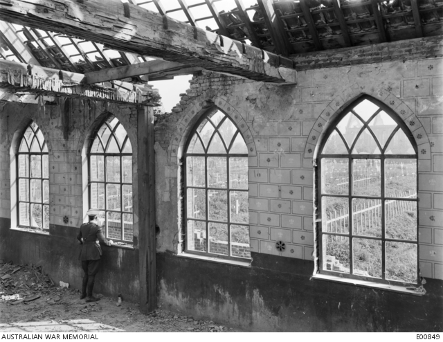 Lieutenant George Hubert Wilkins, an Australian Official Photographer, looking out through the window of the shell damaged village church at Vlamertinghe, near Ypres, upon the graves of many Australian soldiers who made the supreme sacrifice on the battle grounds of the Salient. Belgium: Flanders, West-Vlaanderen, Vlamertinghe. 3 October 1917.