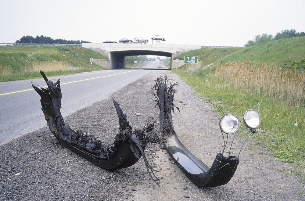 Tire Vessel # 1,  2001 Transport truck tire, water, steel dowelling, truck headlights, wire corseting  105 x 330 x 65 cm