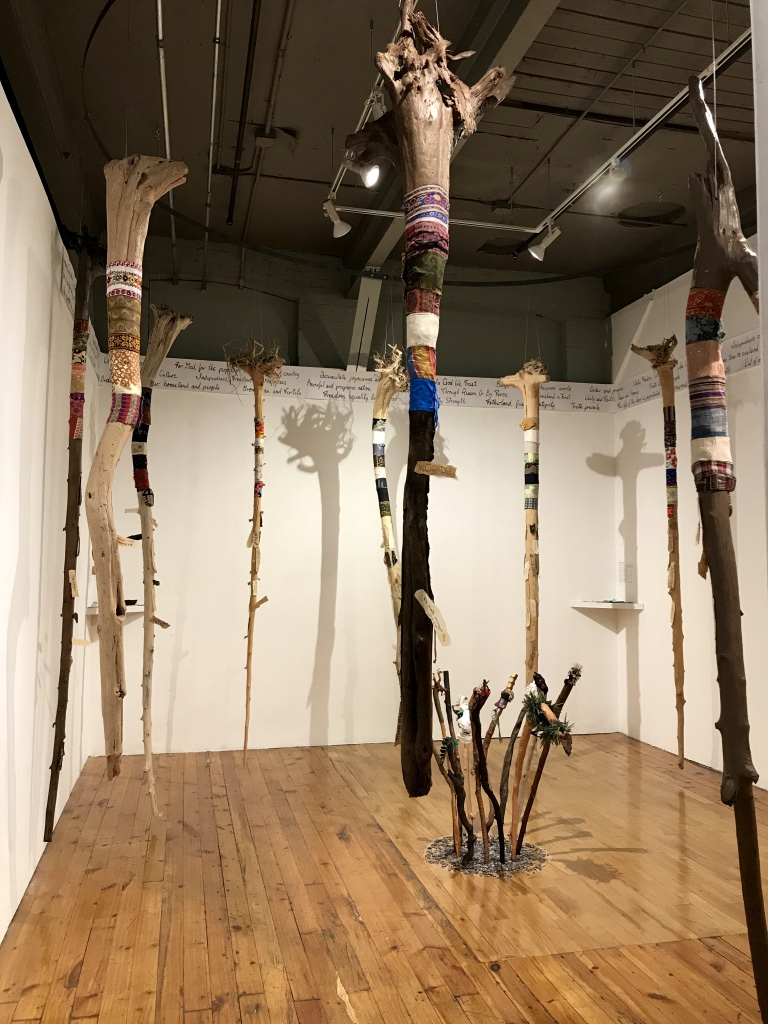 "Around The World: Unity in Diversity  , 2017 - 2018 12 driftwood tree trunks, multi-cultural fabrics, paper ""barks"" Installation view at the Red Head Gallery"